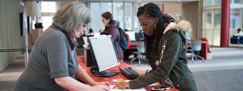 Une étudiante est aidée par une agente de la référence à la bibliothèque HEC Montréal